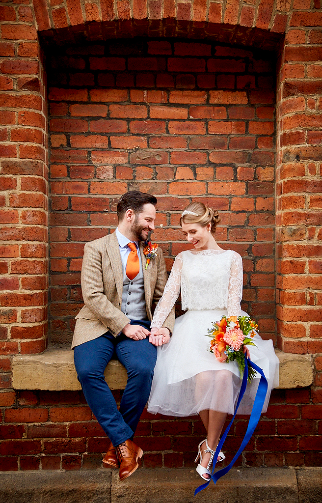 image of bride and groom relaxing in a bricked-up window ledge in Leeds city centre